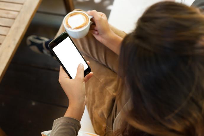 אישה מחזיקה בטלפון נייד, אילוסטרציה (למצולמת אין קשר לנאמר בכתבה)