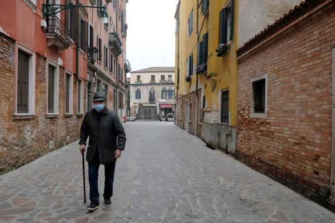 הקורונה: מבוגר עוטה מסכה ברחוב שומם בונציה