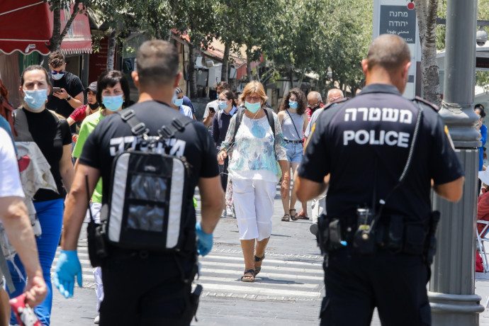 שוטרים אוכפים את הנחיות ההתקהלות לנגיף הקורונה