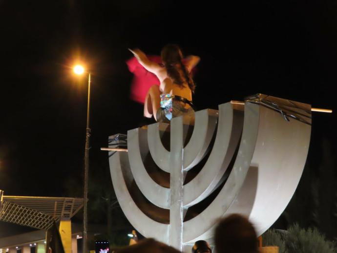 מפגינה מתערטלת על סמל המנורה בכנסת