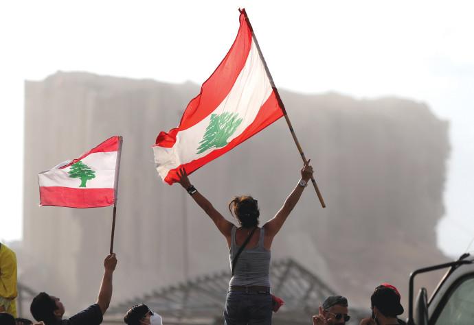 תושבי ביירות ברקע הריסות הנמל לאחר הפיצוץ