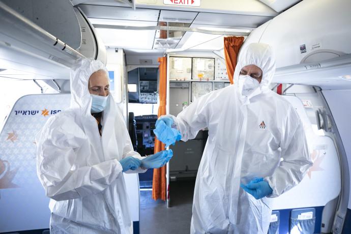 קורונה - דיילים לובשים בגדי הגנה במהלך טיסה לאילת