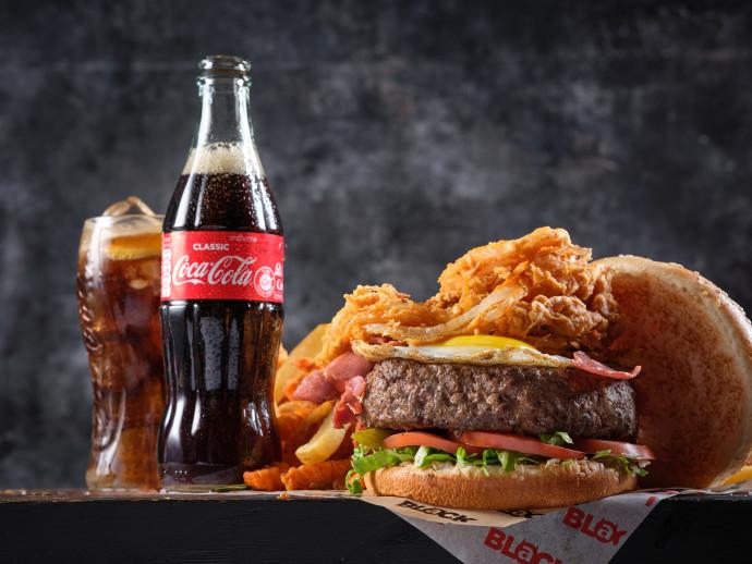 המבורגר של בלאק לצד משקה קוקה-קולה