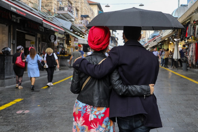 זוג מחובק עם מטריה, מחנה יהודה בגשם (למצולמים אין קשר לכתבה)