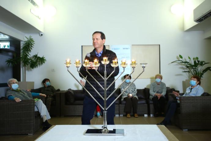 יצחק הרצוג מדליק נרות עם דיירי בית גיל הזהב עמיגור בקריית אונו
