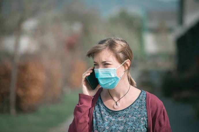 אישה עם מסכה מדברת בטלפון