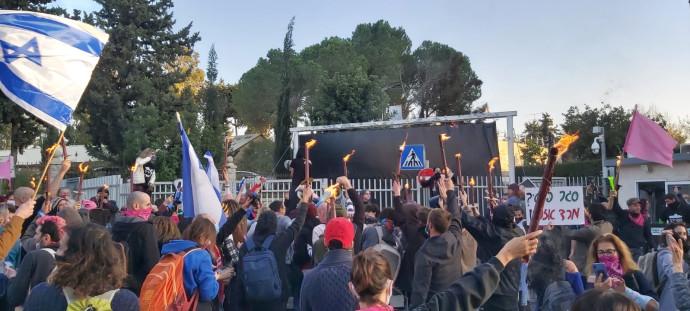 המפגינים מבעירים לפידים סמוך למחסום