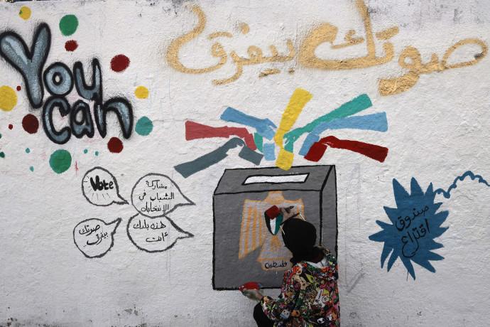 פלסטינית לצד גרפיטי בנושא הבחירות