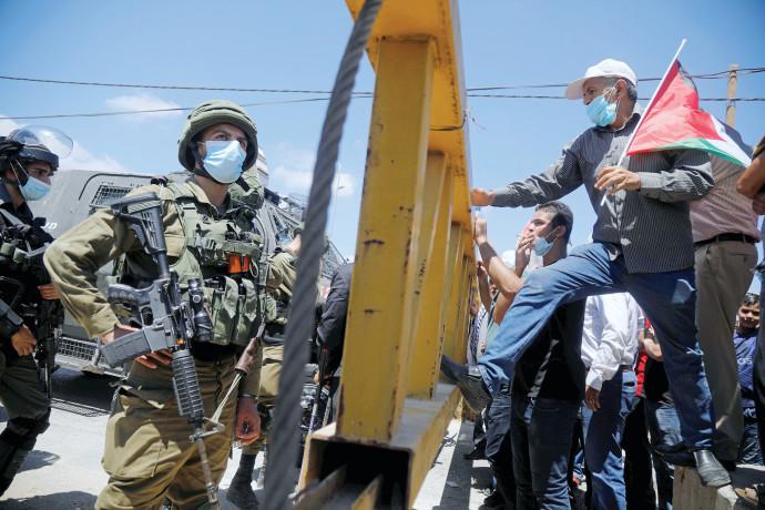 """מפגינים פלסטינים מול חיילי צה""""ל"""