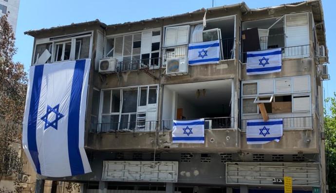 """דגלי ישראל על הבניין שנפגע מרקטה בר""""ג"""
