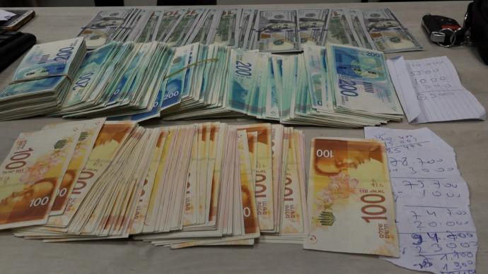 כסף שנמצא בפשיטה של המשטרה על ביתם של חשודים