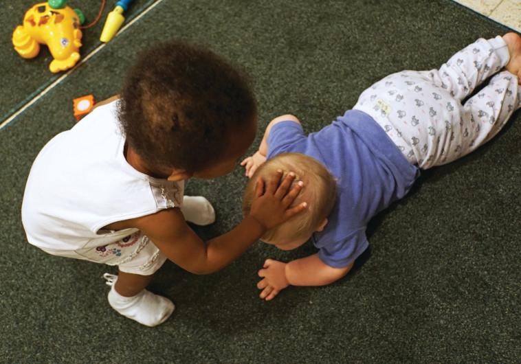 ילדה מלטפת תינוק, אילוסטרציה (למצולמים אין קשר לכתבה)