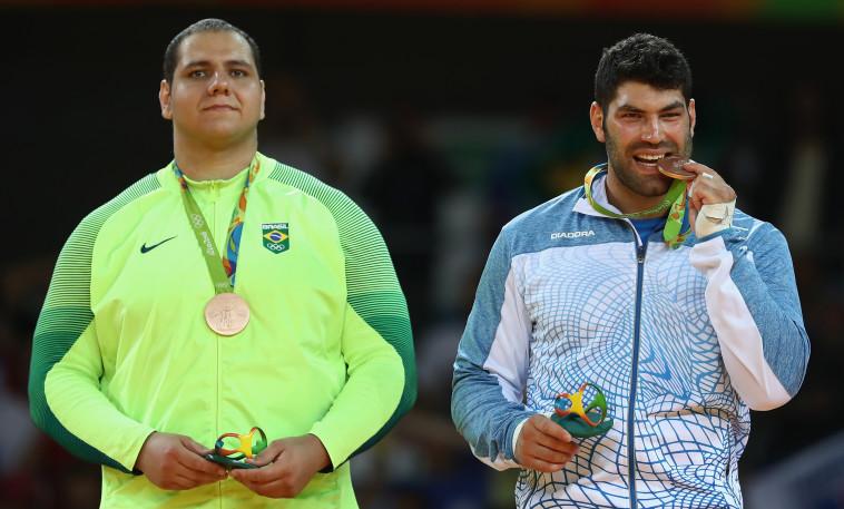 אורי ששון טועם את המדליה, צילום: Getty images