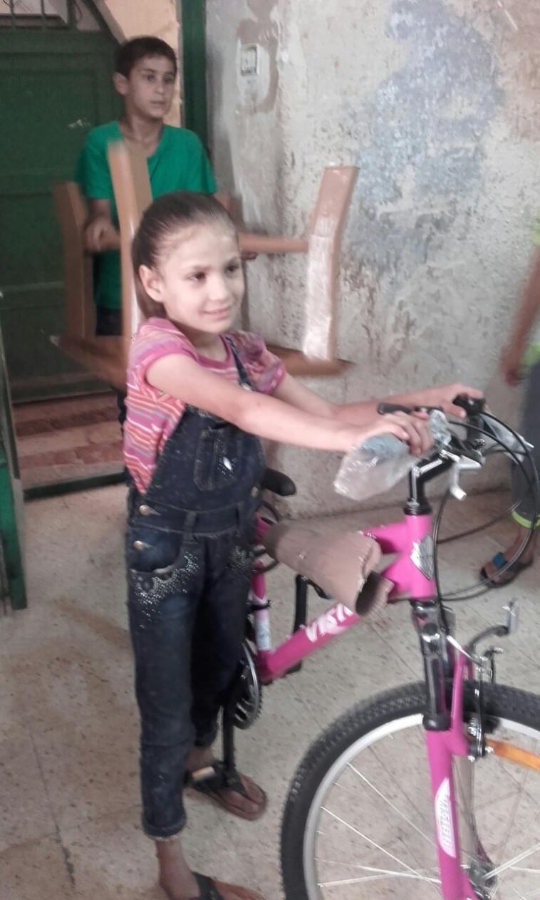 אנואר בוראן עם האופניים שקיבלה מסמי יולס