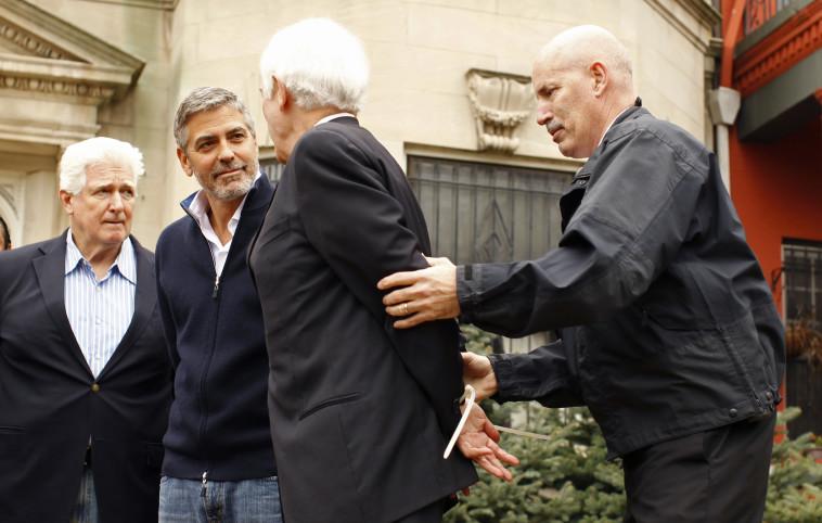 ג'ורג' קלוני ואביו ניק נעצרים בהפגנה נגד עומר אל־בשיר מול שגרירות סודן בוושינגטון. צילום: רויטרס