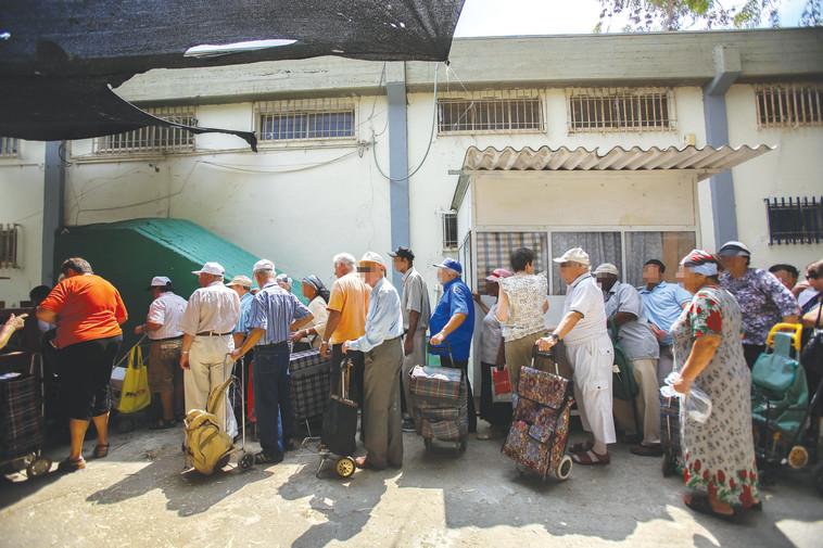 נזקקים עומדים בתור לחלוקת מזון. צילום: יונתן זינדל, פלאש 90