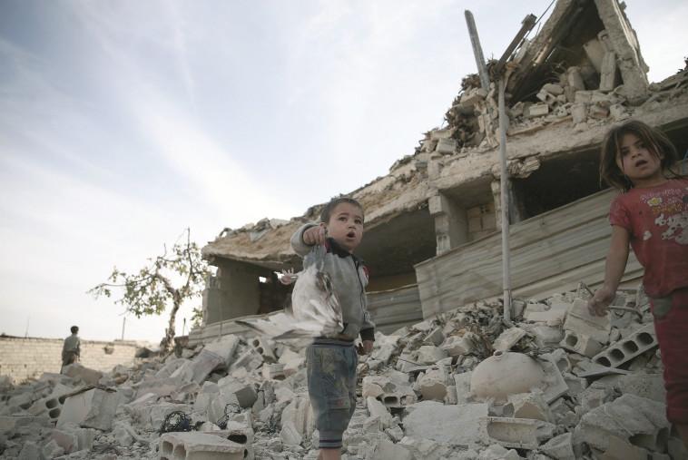 """""""אין סוריה, אבל יש עם סורי מפולג"""". ילדים לאחר הפצצת שכונה בדמשק. צילום: רויטרס"""