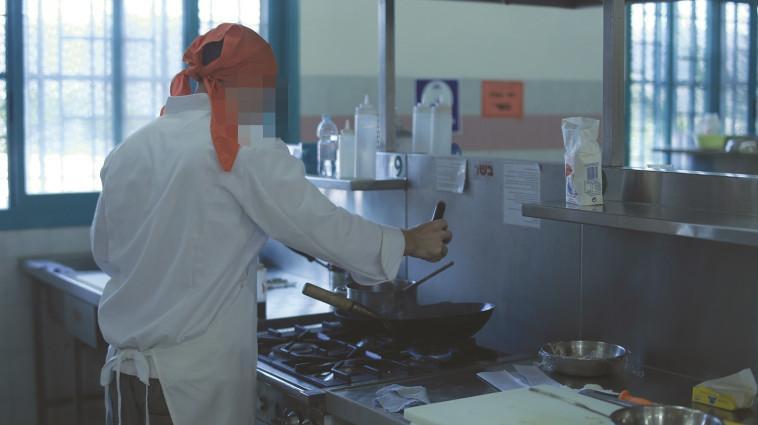 לומדים מושגי בישול מורכבים, אסיר מבשל בזמן הקורס. צילום: תמיר למפרט