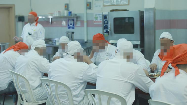 האסירים אוכלים את שבישלו בסיום היום. צילום: תמיר למפרט