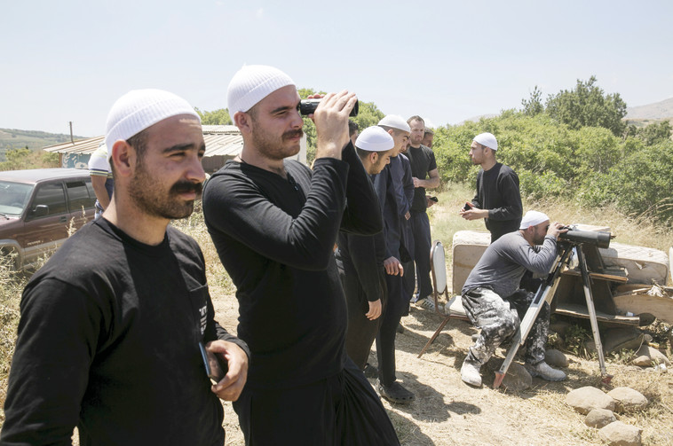 דרוזים בצד הישראלי של הגבול משקיפים על הלחימה בכפר הדרוזי חאדר בצד הסורי. צילום: רויטרס