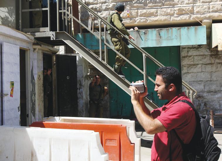 פעיל בצלם בחברון. צילום: רויטרס