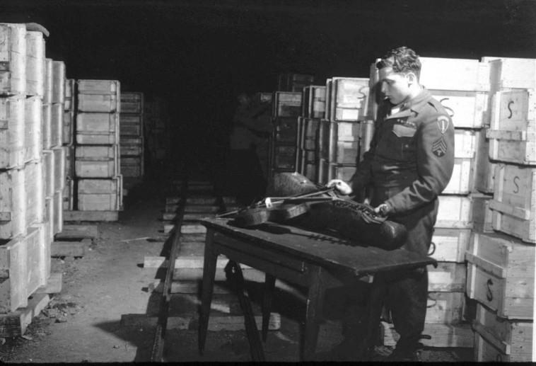 """""""היהודים היו הקליינטים הכי טובים"""". חייל אמריקאי בוחן כינור שהיה שייך ליהודי והוחרם בידי הנאצים, לאחר שחרור המחנות, 1945. צילום: National Archives/gettyimages"""