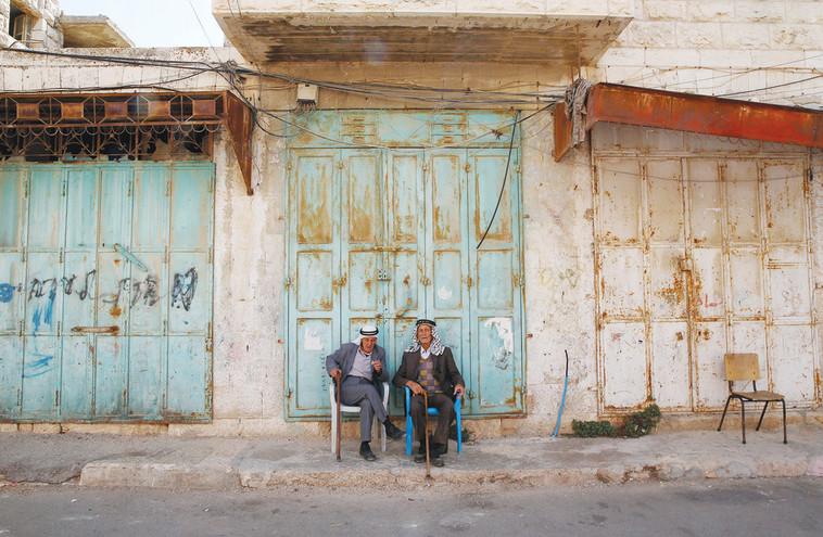 עיר סגורה. פלסטינים ברחוב השוהדא הסגור. צילום: רויטרס