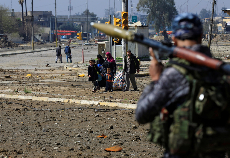חייל צבא עיראק במוסול צופה במשפחה שבורחת מהעיר. צילום: רויטרס