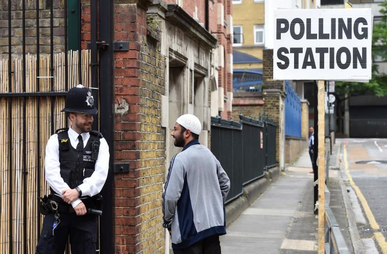 מצביע מוסלמי לצד שוטר בריטי סמוך לקלפי. צילום: רויטרס