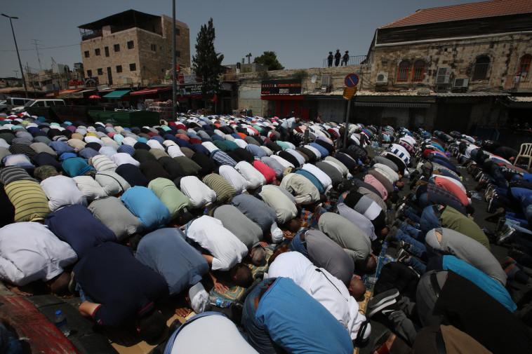 מוסלמים מתפללים מחוץ לשער שכם (צילום: מרק ישראל סלם)