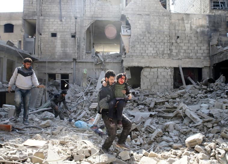 ילד מפונה מההריסות אחרי תקיפה בע'וטה. צילום: רויטרס