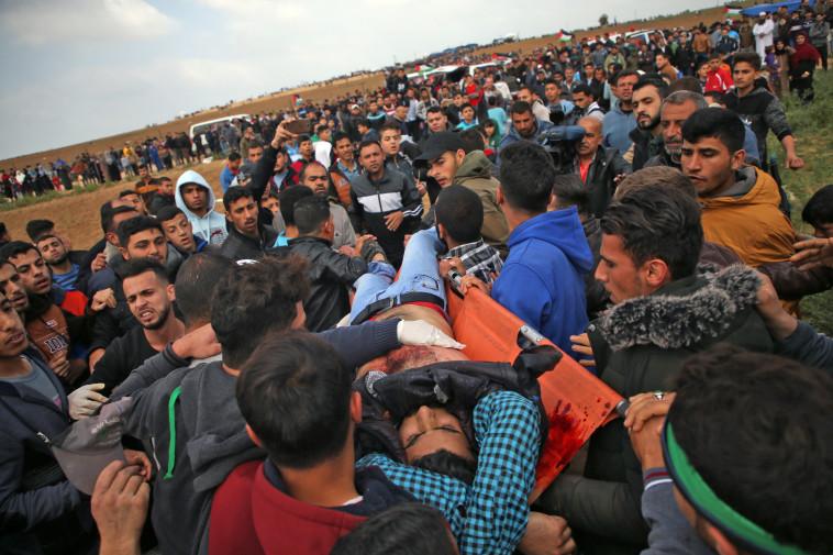 פצוע פלסטיני מפונה במהלך ההפגנה, צילום: AFP