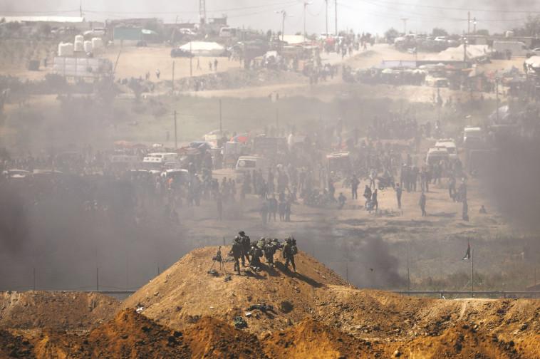"""חיילי צה""""ל מול מפגינים פלסטינים בגדר רצועת עזה. צילום: רויטרס"""