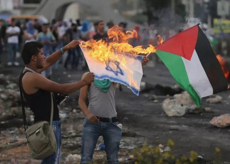 מפגינים פלסטינים שורפים דגל ישראל ליד בית אל  (צילום: רויטרס)