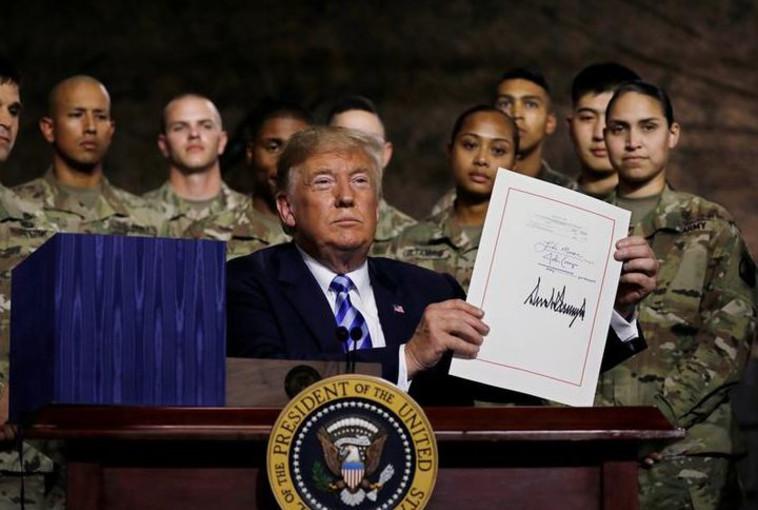 טראמפ מציג את חוק ההסמכה לביטחון לאומי לאחר חתימתו. צילום: רויטרס