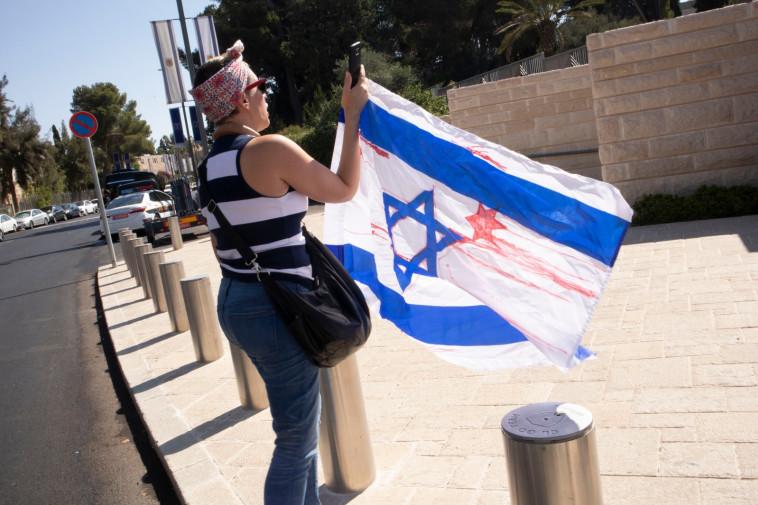 """מפגינה עם דגל ישראל """"מרוח בדם"""". צילום: אסתי דזיובוב/TPS"""