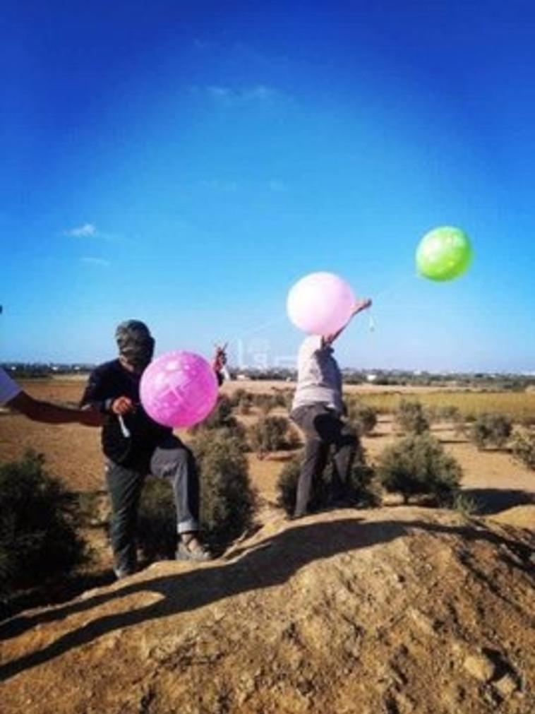 מחבלים משגרים בלוני תבערה בעזה. צילום: רשתות ערביות