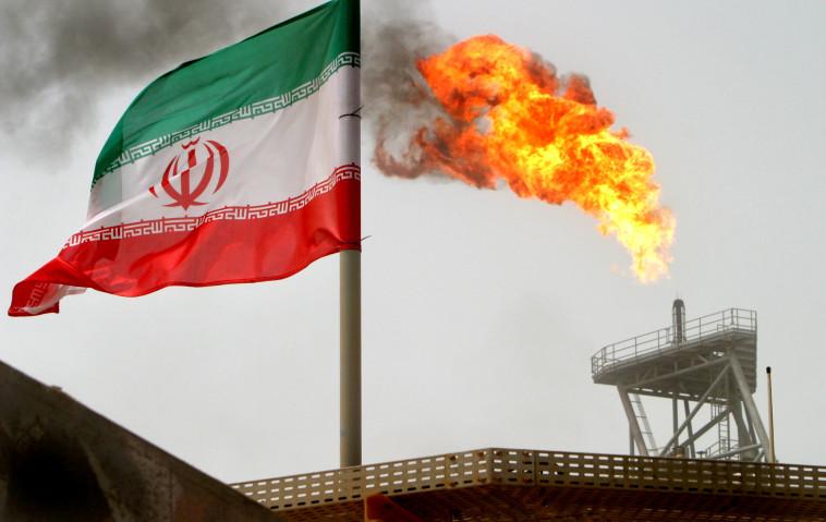דגל איראן על רקע מתקן ייצור נפט במפרץ הפרסי (צילום: רויטרס)