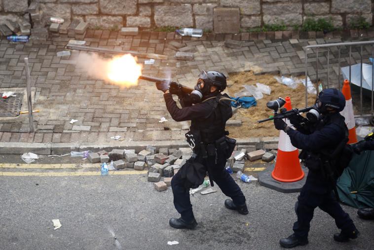 שוטר מנסה לדכא הפגנות בהונג קונג, צילום: REUTERS/Thomas Peter