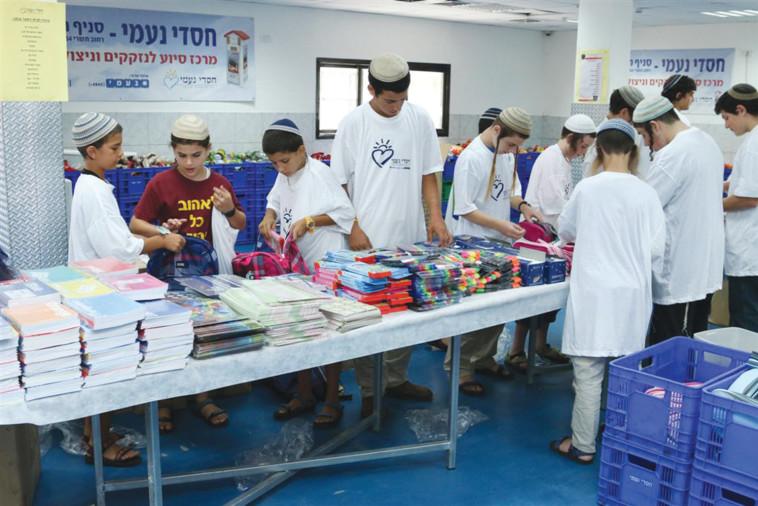 """מתנדבים מכינים תרומות של ציוד לביה""""ס עבור ילדים נזקקים. צילום: חסדי נעמי"""