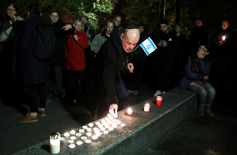 מדליקים נרות לזכר הקרבנות בפיגוע הירי מחוץ לבית הכנסת העיר האלה. צילום: רויטרס