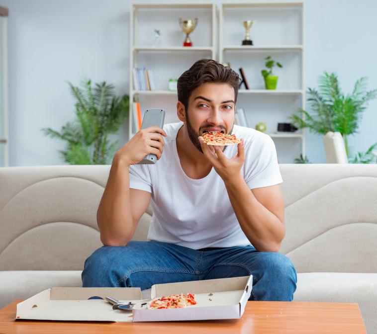 גבר אוכל פיצה בבית מול הטלוויזיה (צילום: ingimage ASAP)