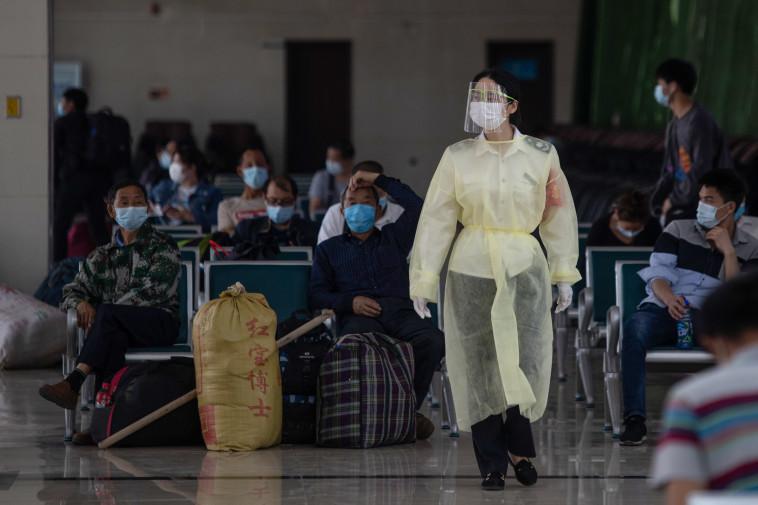 קורונה - אנשים ממתינים לאוטובוס בעיר ווהאן שבסין (צילום: STR/AFP via Getty Images)
