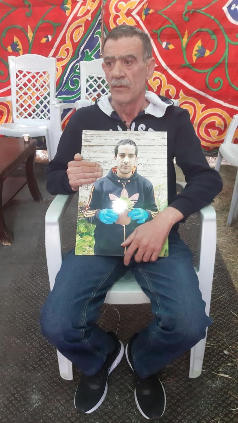 אביו של איאד אלחלאק מחזיק תמונה שלו (צילום: באדיבות המשפחה)