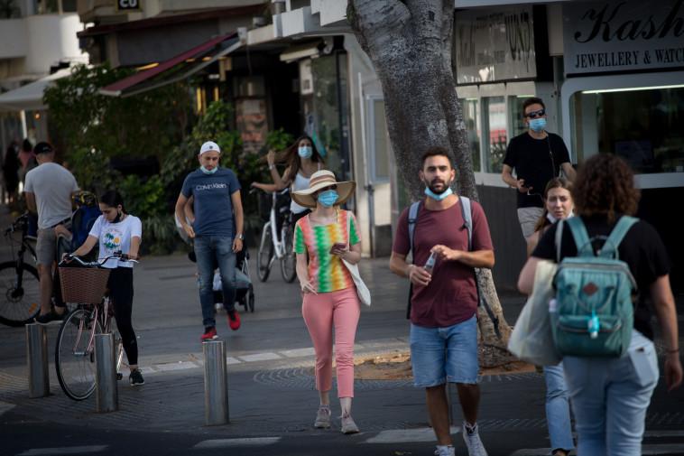 אנשים ברחוב מזלזלים בהנחיות חבישת מסכה (צילום: מרים אלסטר, פלאש 90)