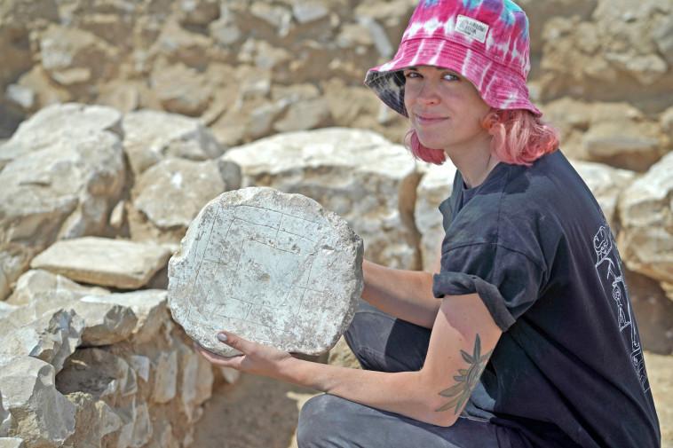 סטודנטית שלקחה חלק בחפירות עם לוח משחק הטחנה (צילום: אמיל אלג'ם, רשות העתיקות)