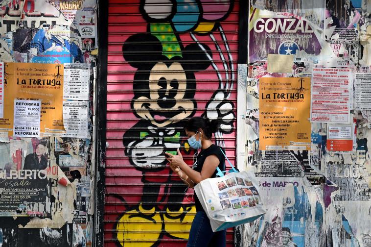 קורונה - אישה עם מסכה ברחובות מדריד (צילום: GABRIEL BOUYS/AFP via Getty Images)