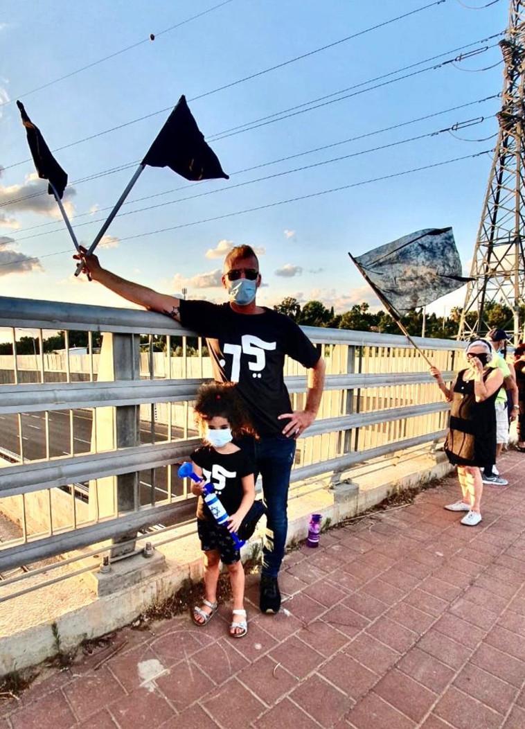 אב ובתו מפגינים (צילום: דוברות מחאת הדגלים השחורים)