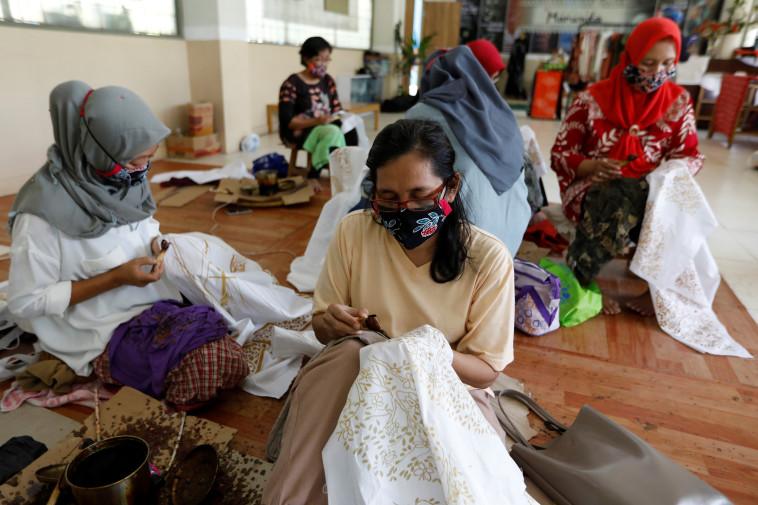 אינדונזיה: נשים עובדות ברקמה על שמלות בג'קרטה (צילום: REUTERS/Willy Kurniawan)