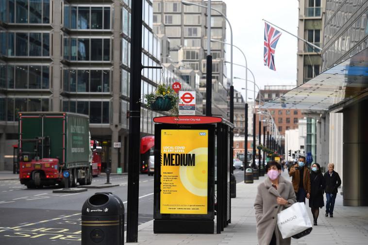 קורונה - אנשים עם מסכה ברחובות לונדון (צילום: JUSTIN TALLIS/AFP via Getty Images)